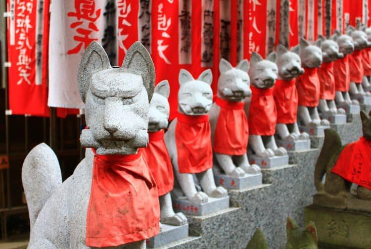 Rangée statues renard pierre bavoir rouge