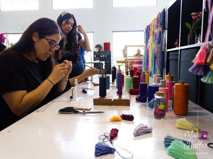 Guests are sitting at a Mad Hatter Warped & Woven work table making yarn tassels in all colours. There are spools of thread, tassels, scissors, and other supplies on the table. Guests look concentrated in their tassel making.