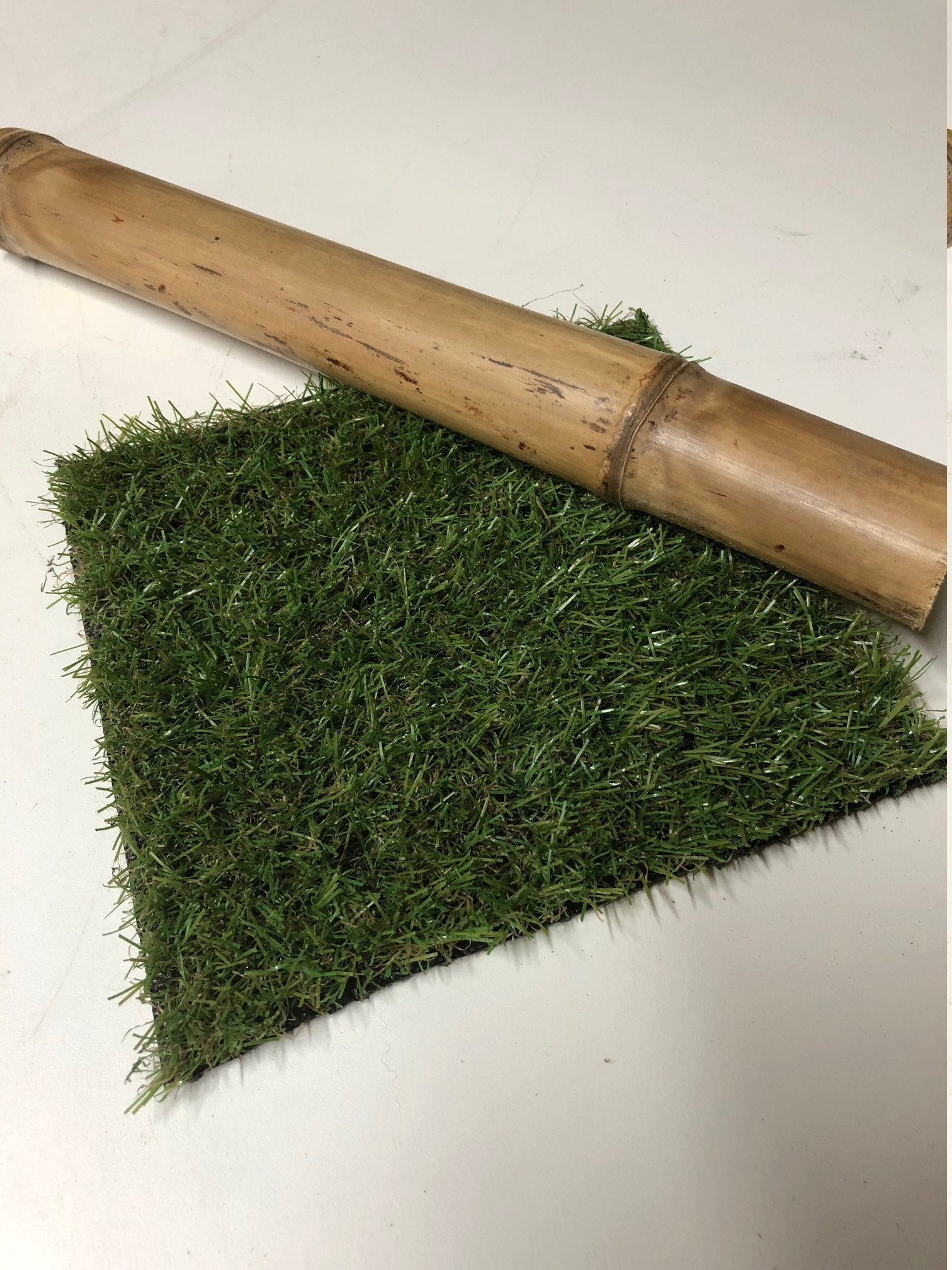 Artificial grass off-cut and a piece of bamboo