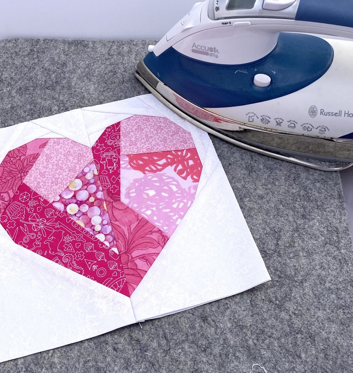 A beautiful foundation paper pieced heart being pressed by an iron before setting into a quilt.