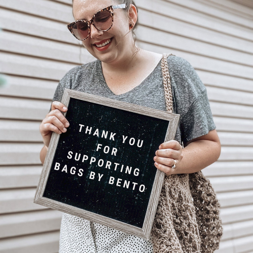 Woman holding a sign that says thank you for supporting Bags by Bento