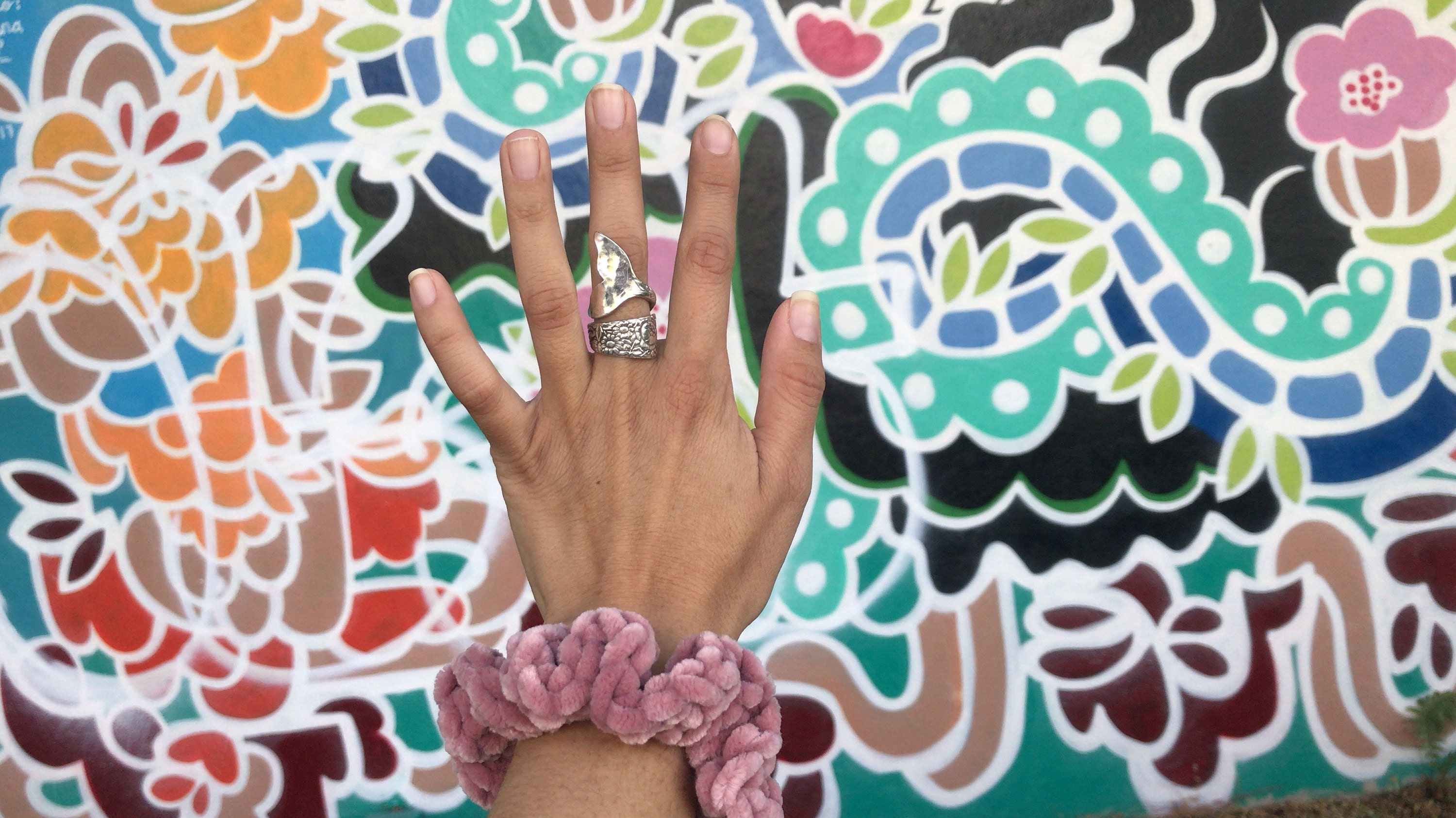 Mermaid ring by Avalonia Jewelry displayed against street art a Wynwood Walls Miami. Pink velvet scrunchy by Knot For U also featured.