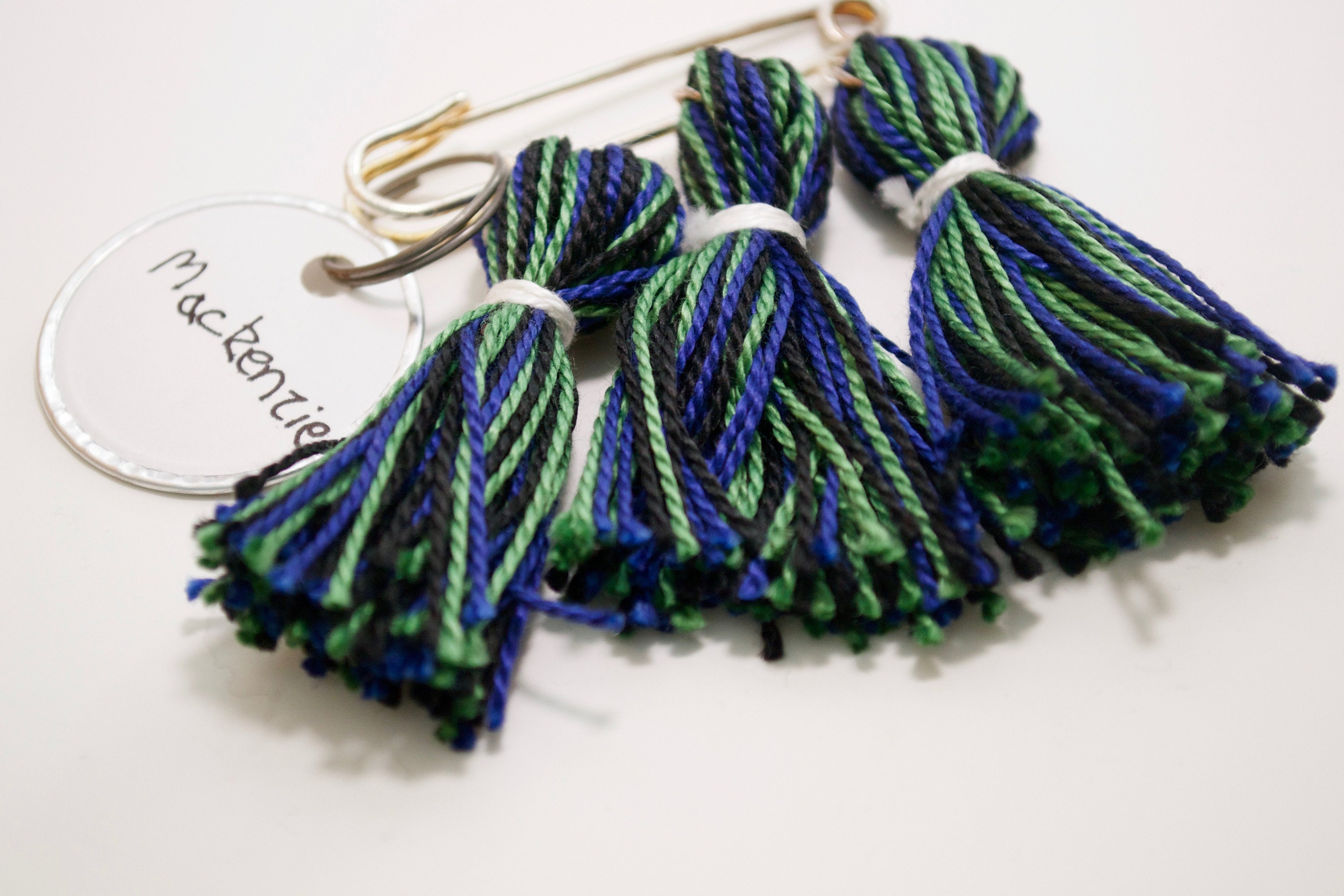 Mackenzie tartan tassel kilt pin in blue, black, and green, with white wrap