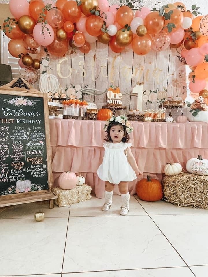 Baby on their first birthday surrounded by pumpkin themed backdrop