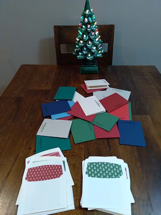 Christmas cards and envelopes spread out on a table