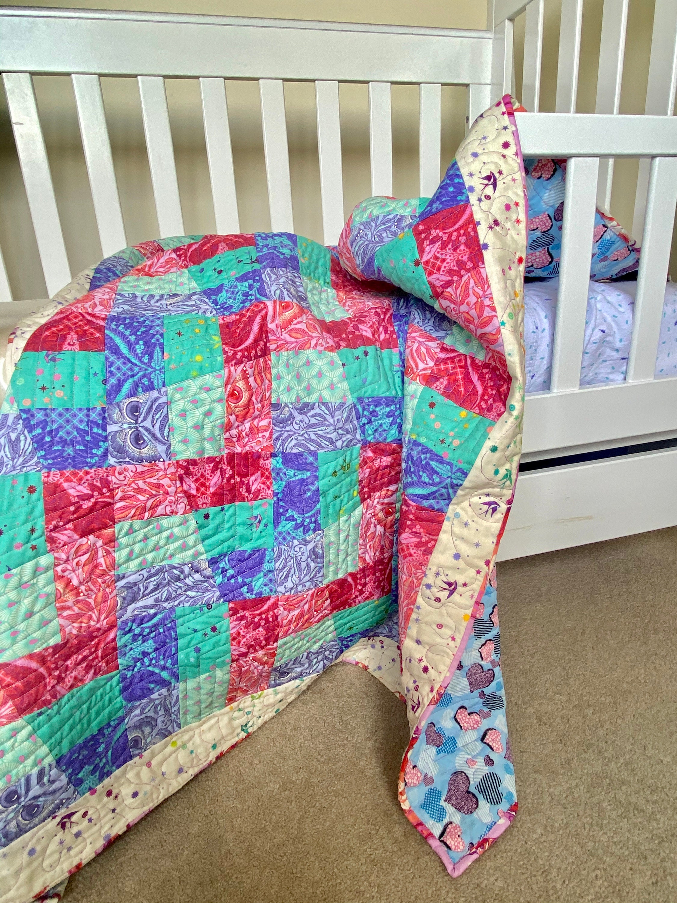Machine Pieced Quilt draped over a toddler bed