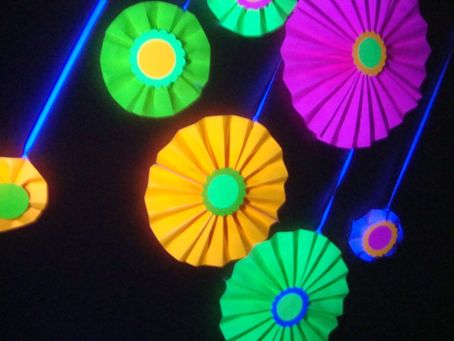 neon poster board folded into paper rosettes for a black light glow party
