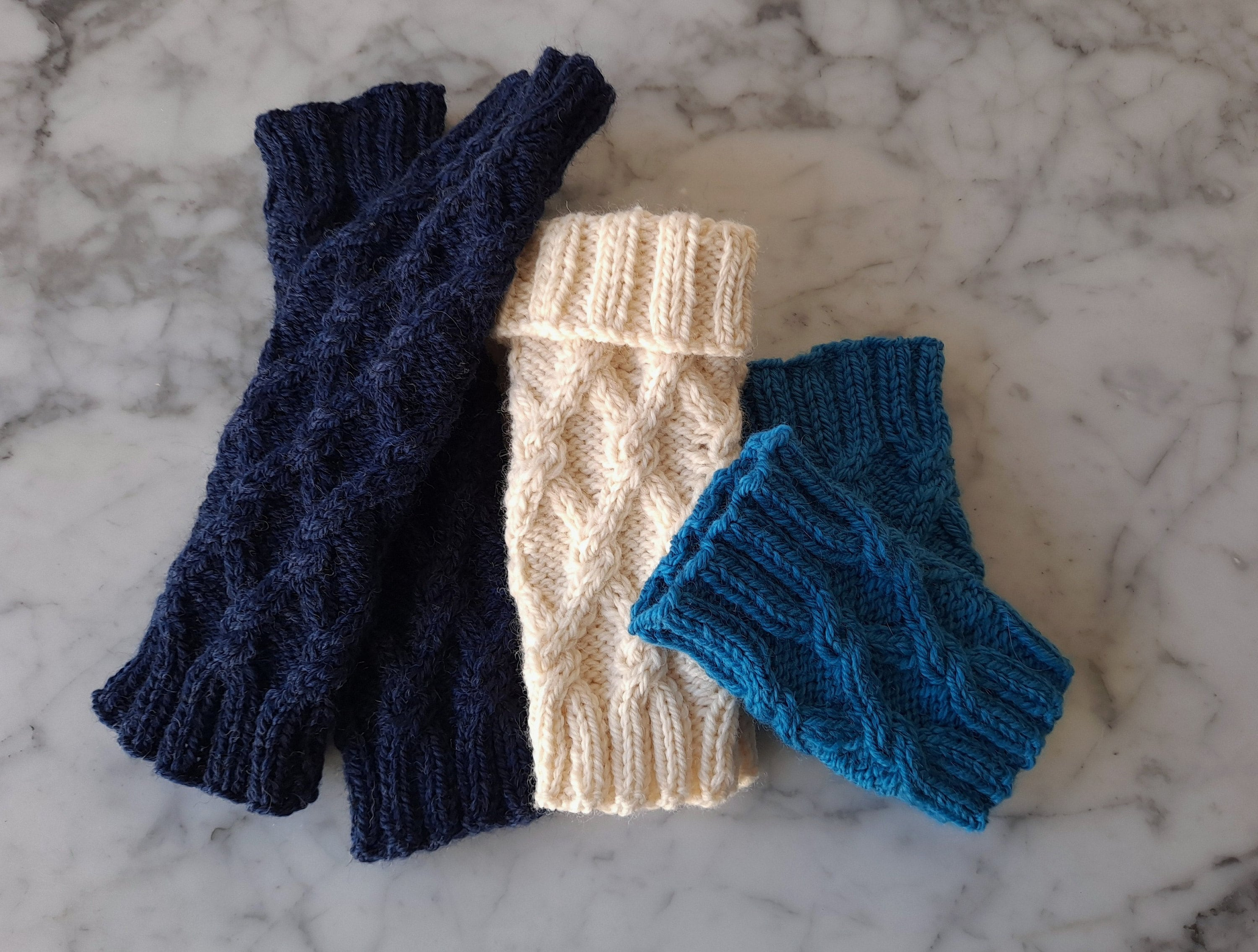 Three pairs of knittted wristwamers are displayed laid flat; the mittens are in different sizes and lengths.