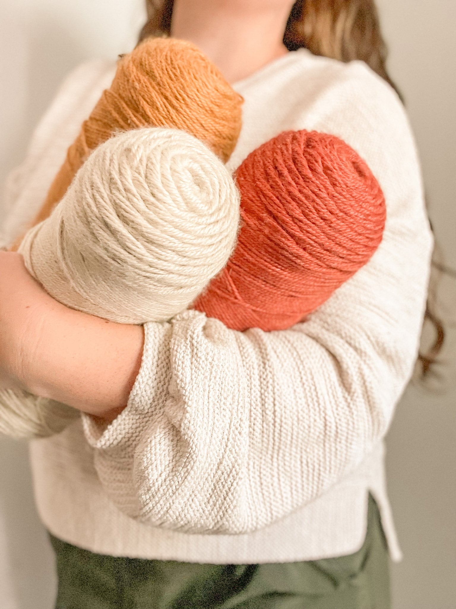 Woman holding three skeins of yarn in Fall colors