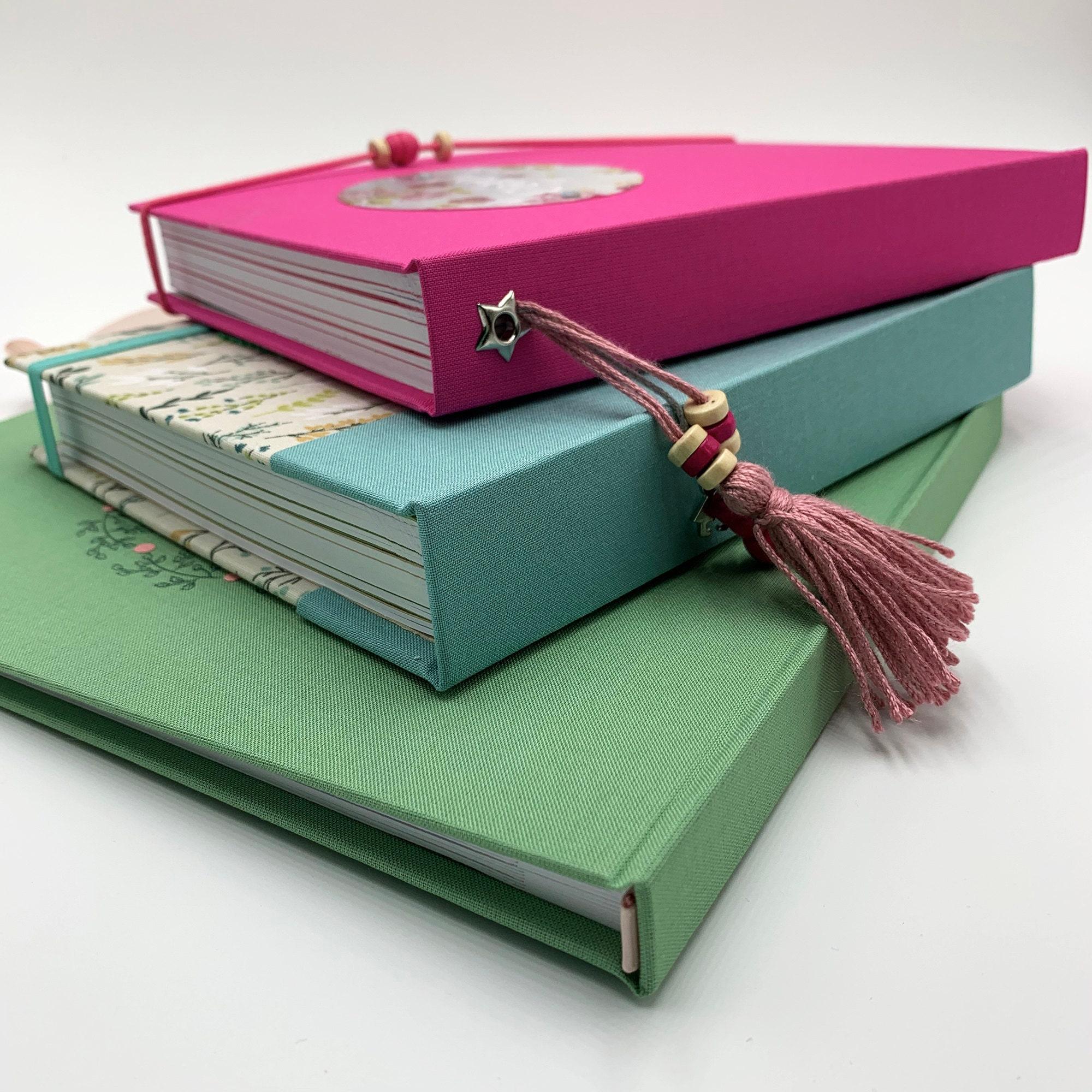 Imagen con tres álbums y cuadernos de b-paper con el lomo recto