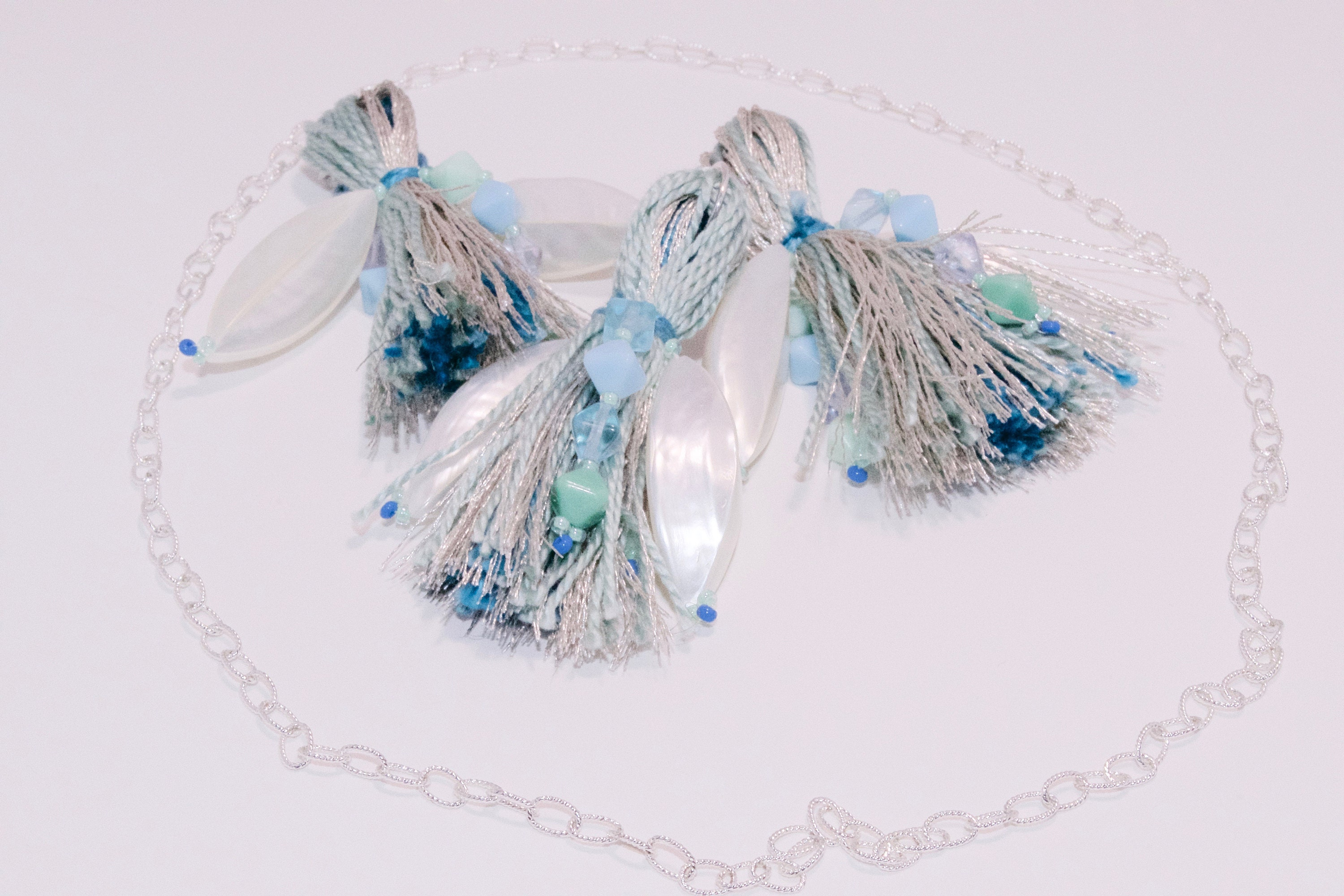 Three tassels in silver and sea green with a large pearlescent bead each and a silver chain around them