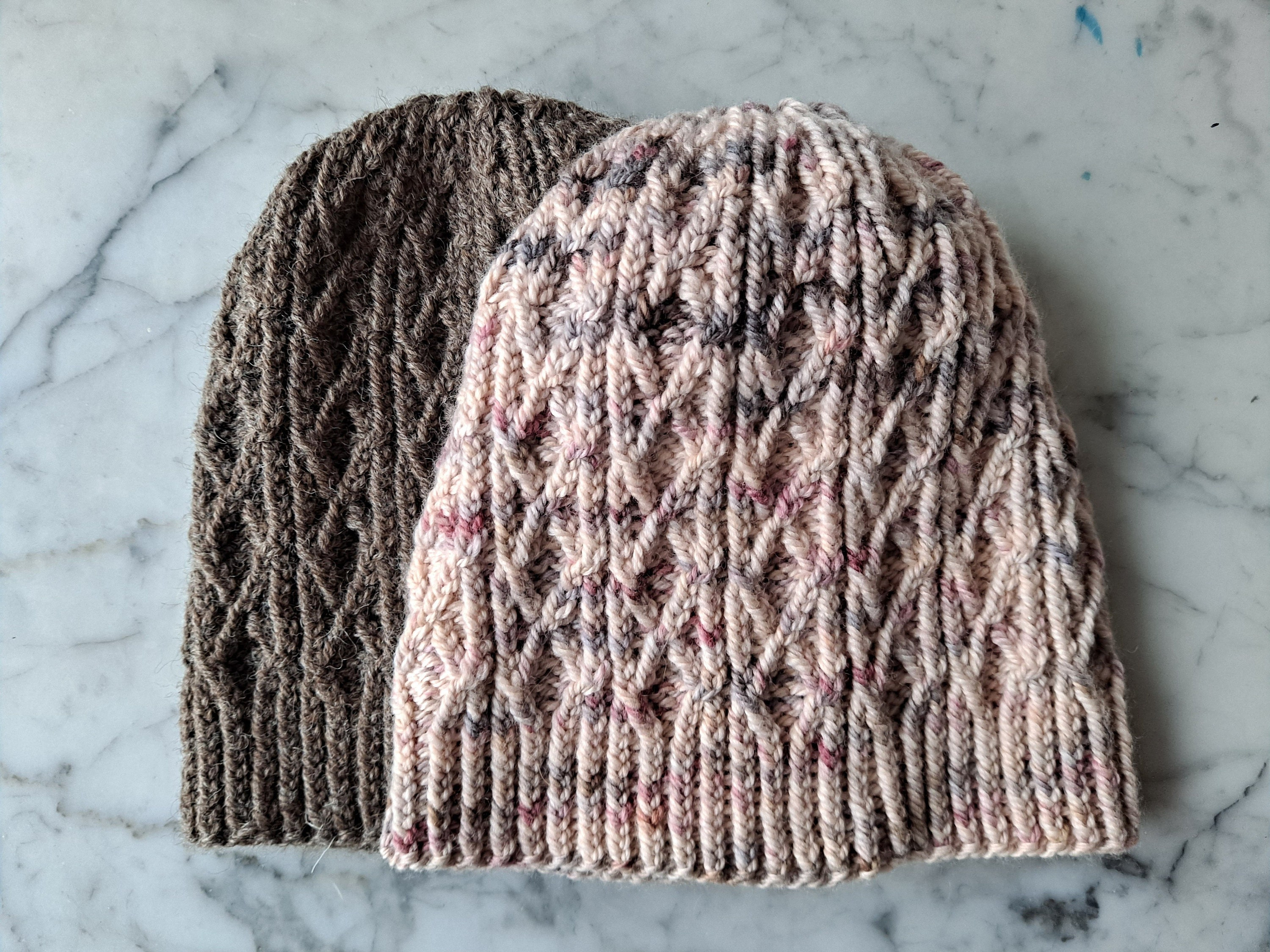 Burren Beanie: two hats lie flat on a marble background. Both feature a cabled lattice pattern.