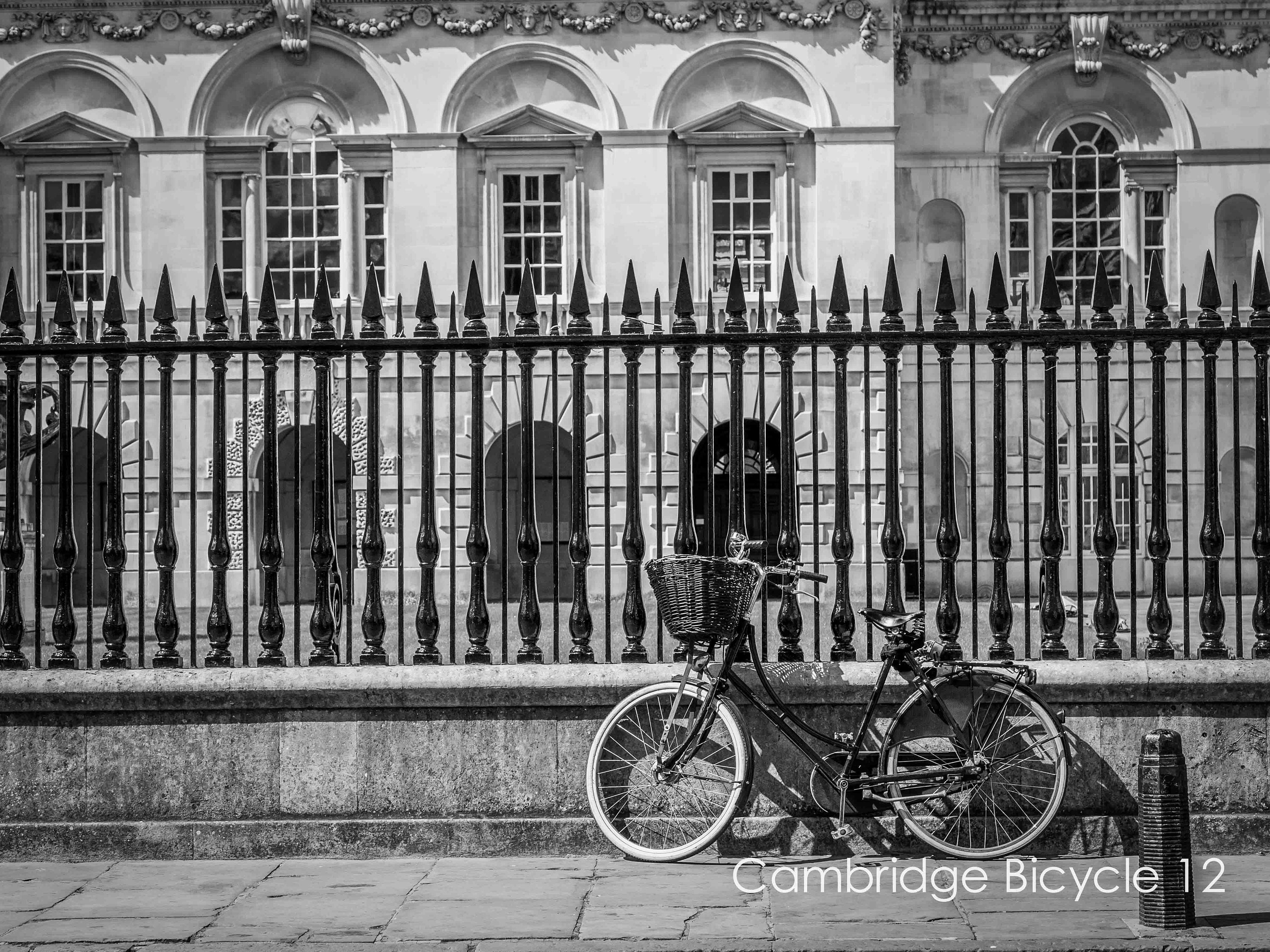 cambridge wall art in black and white of bicycle parked in front of the old schools with a wicker basket in custom sizes and limited edition or ready to hang wall art