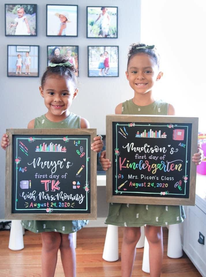two girls holding back to school boards