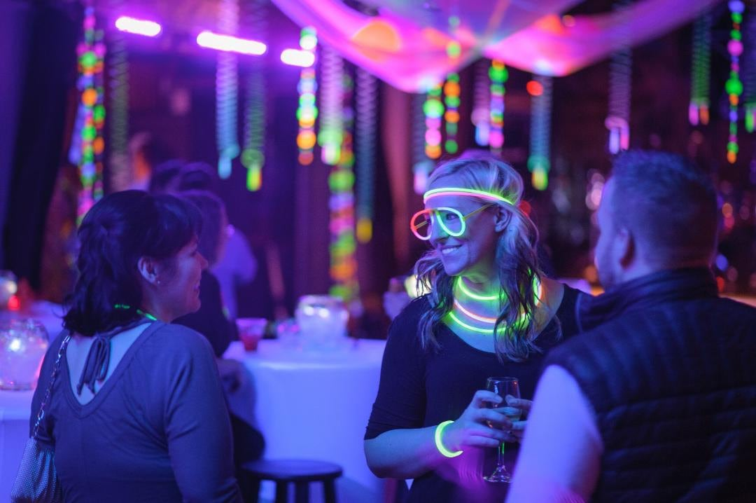 people with glow bracelets, necklaces, and glasses at black light glow party