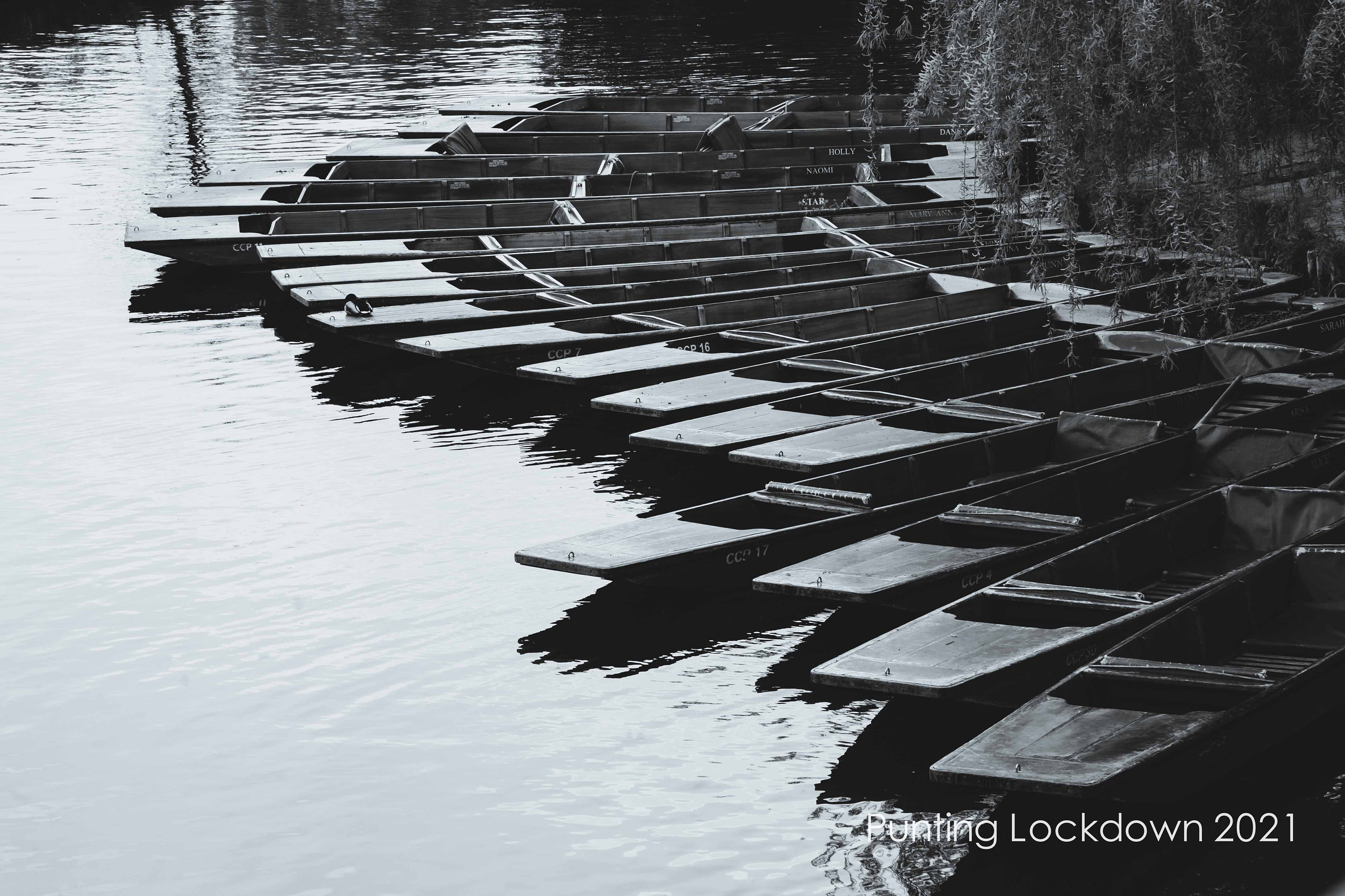black and white limited edition prints of empty punts lined up on the river cam in Cambridge available in custom sizes, unframed or ready to hang like canvas, art panel and box frame