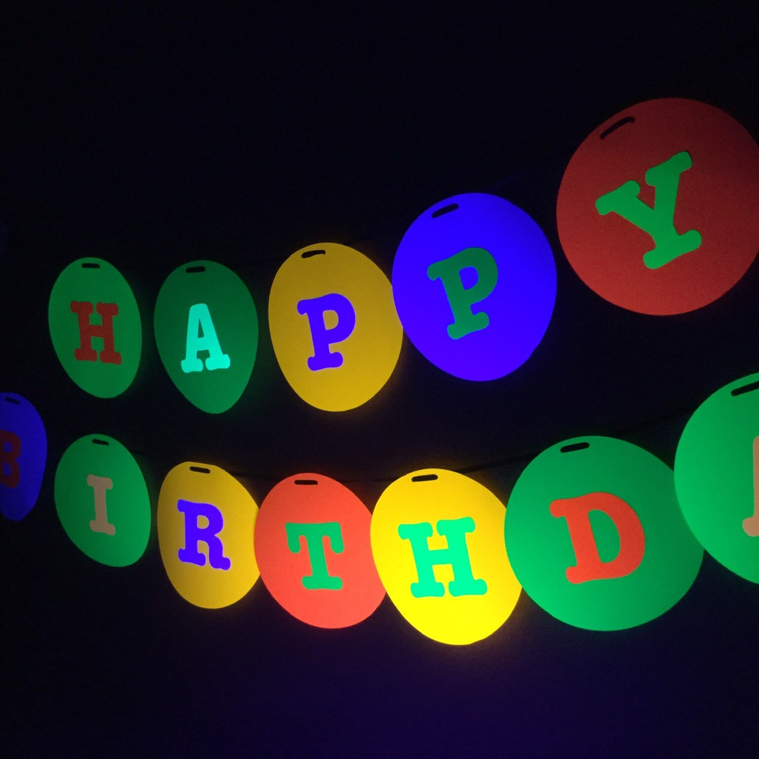 large 8 circle with letters to spell HAPPY BIRTHDAY in neon colors for glow black light party