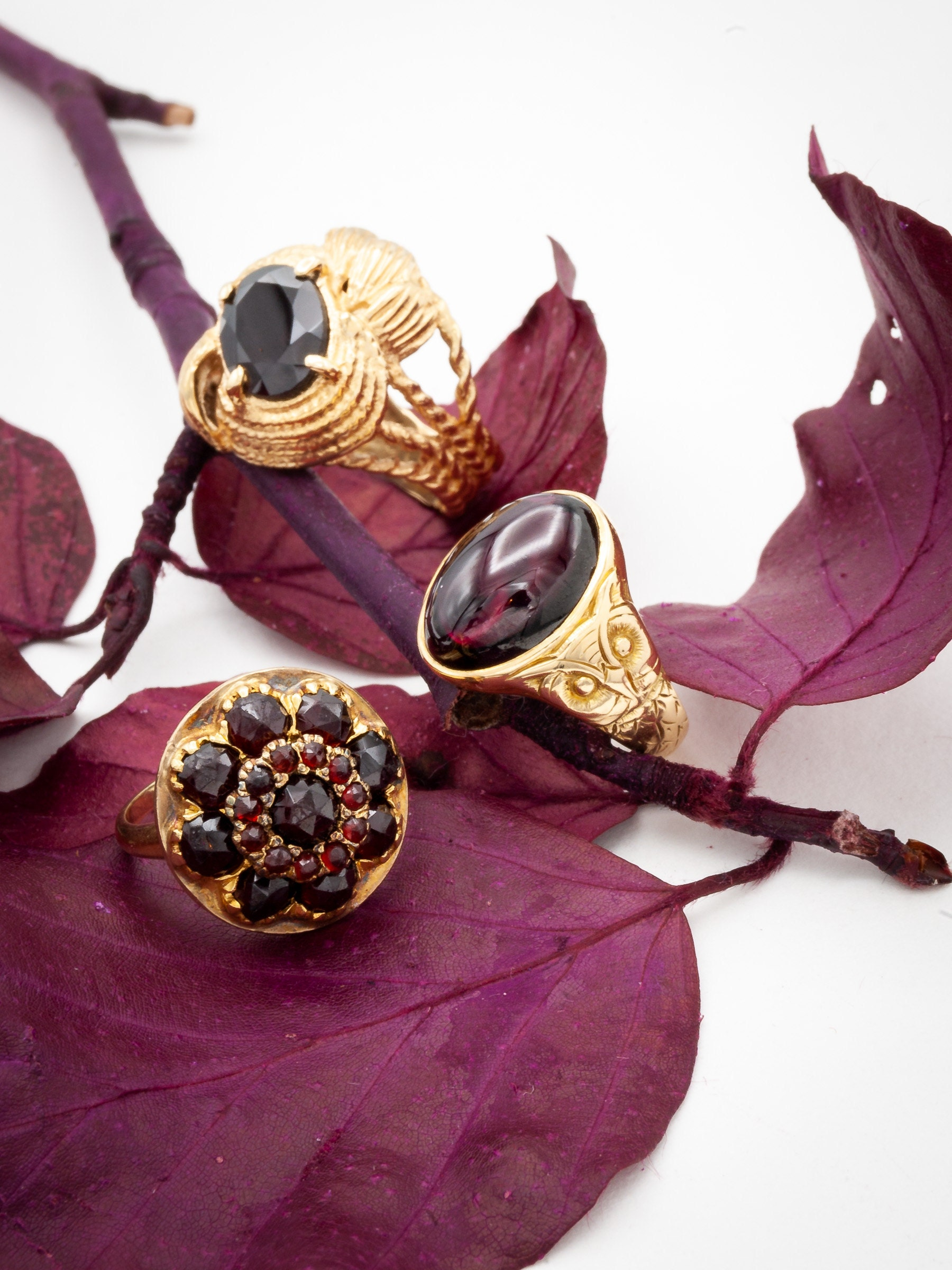 Three Garnet and Gold Vintage Rings with Cabochon and Faceted gemstones on Wine Red Leaves