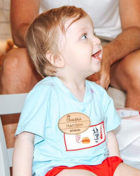 A toddler with a wondrously curious expression, wearing a maple hardwood chick-fil-a name tag and a Chick-fil-A t-shirt