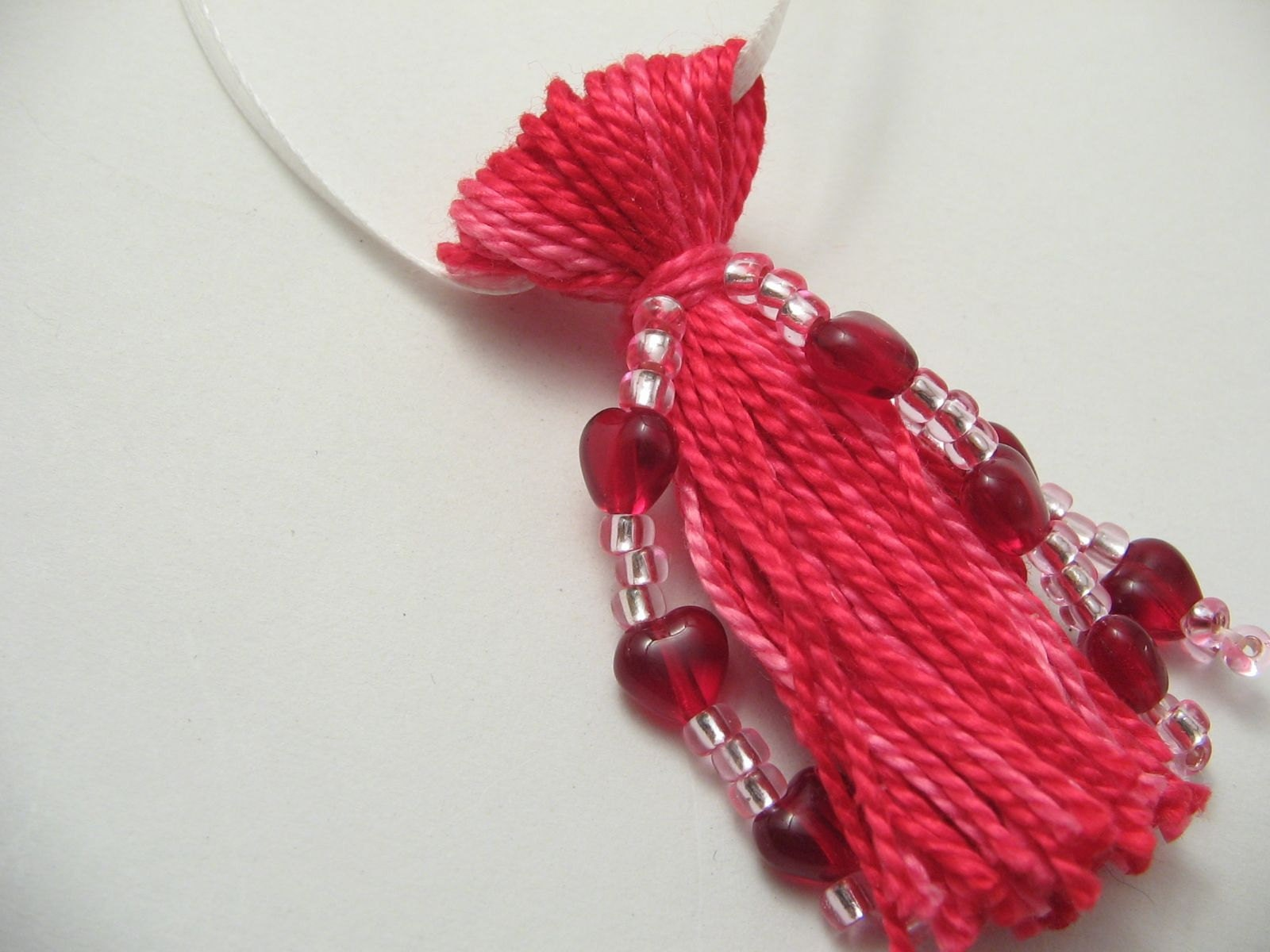 Pink tassel beaded with red glass hearts and white satin ribbon hanger