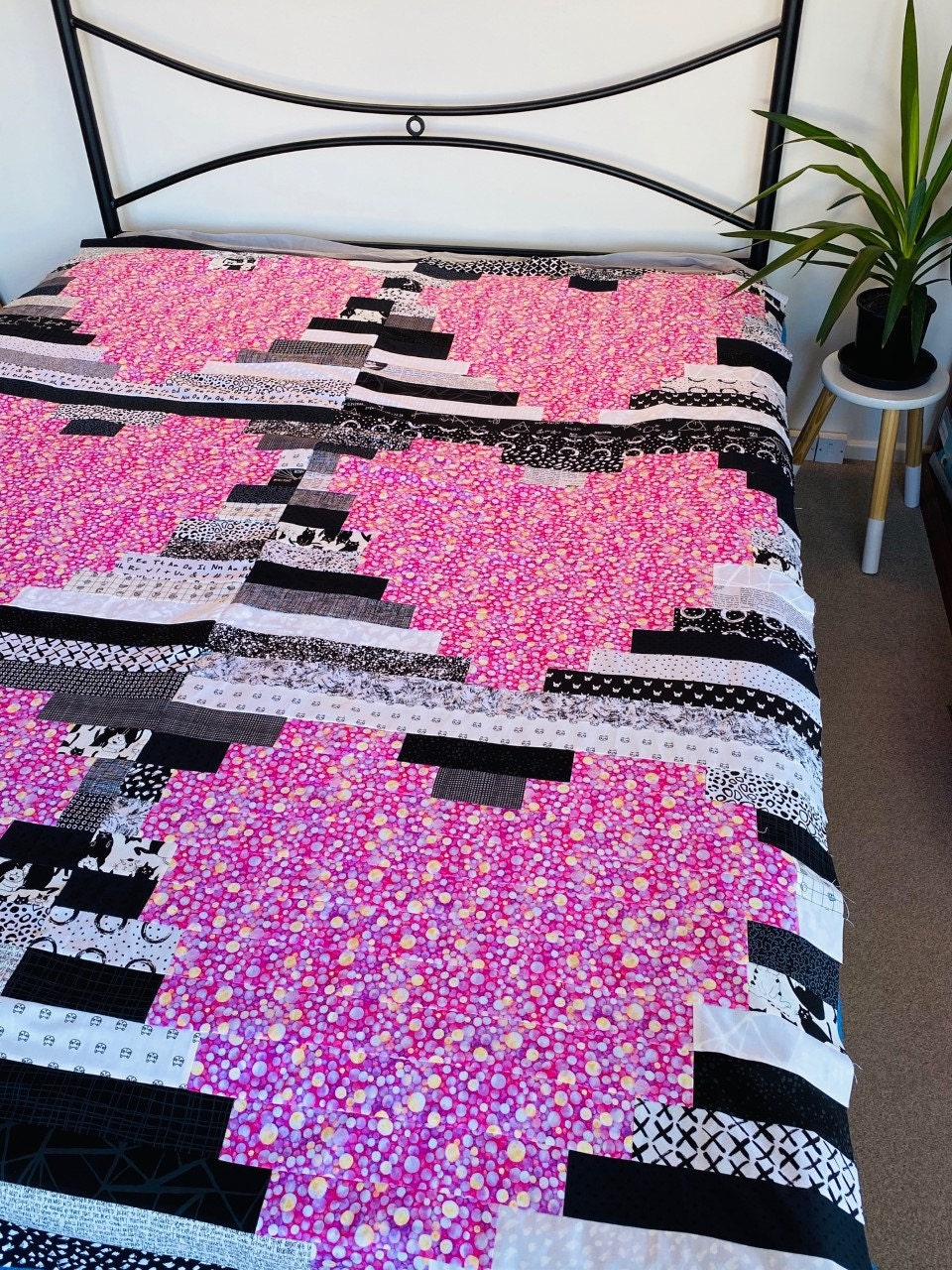 Photo of a Heart Quilt spread out over a bed. This quilt is called Heart Strings, by Alexa & Me.