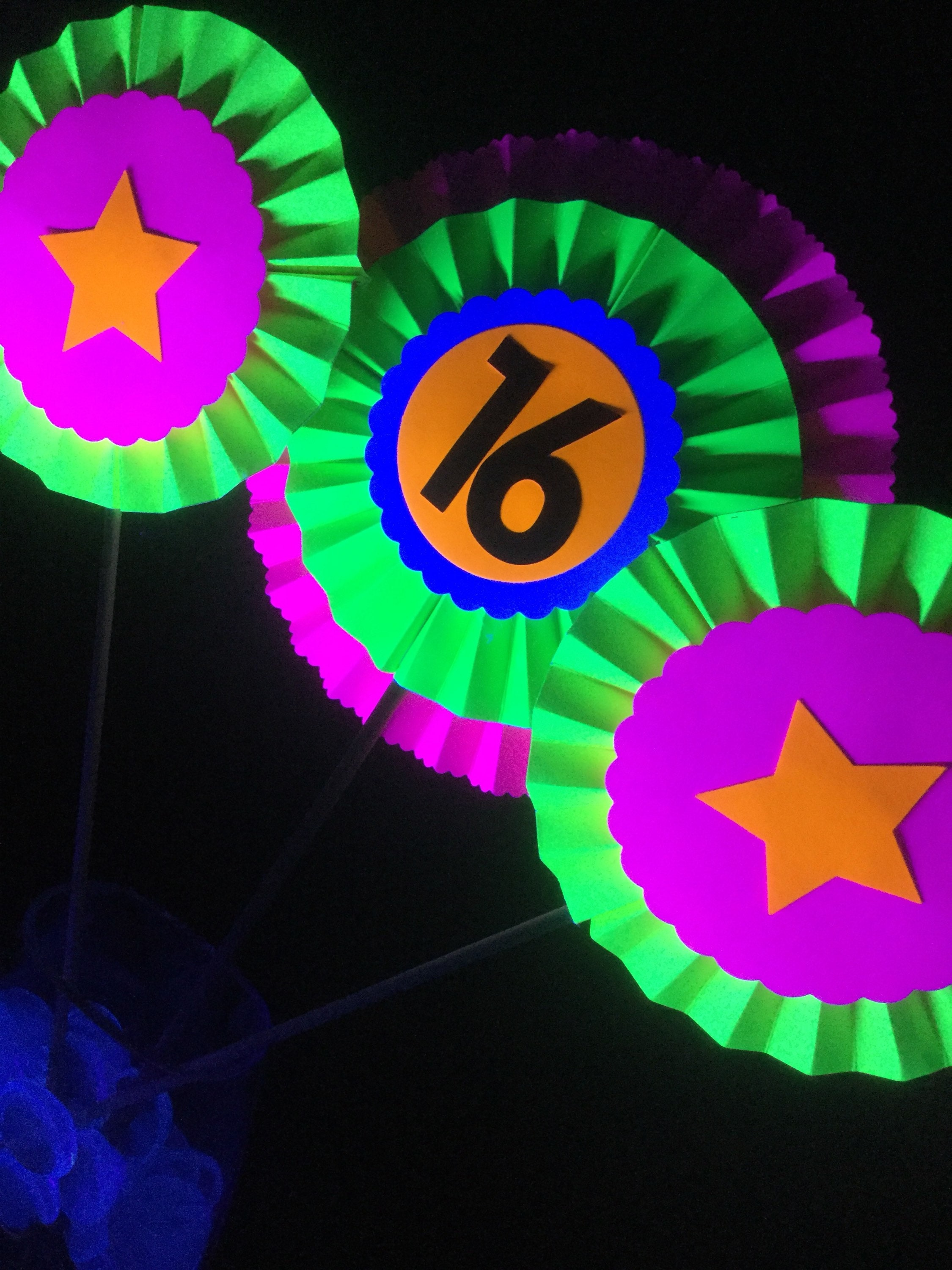 neon medallions on sticks with the number 16 for a centerpiece at a black light glow party