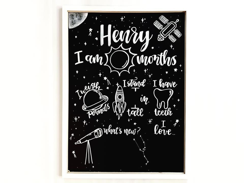Pictured here is a space themed milestone chalkboard with white ink.