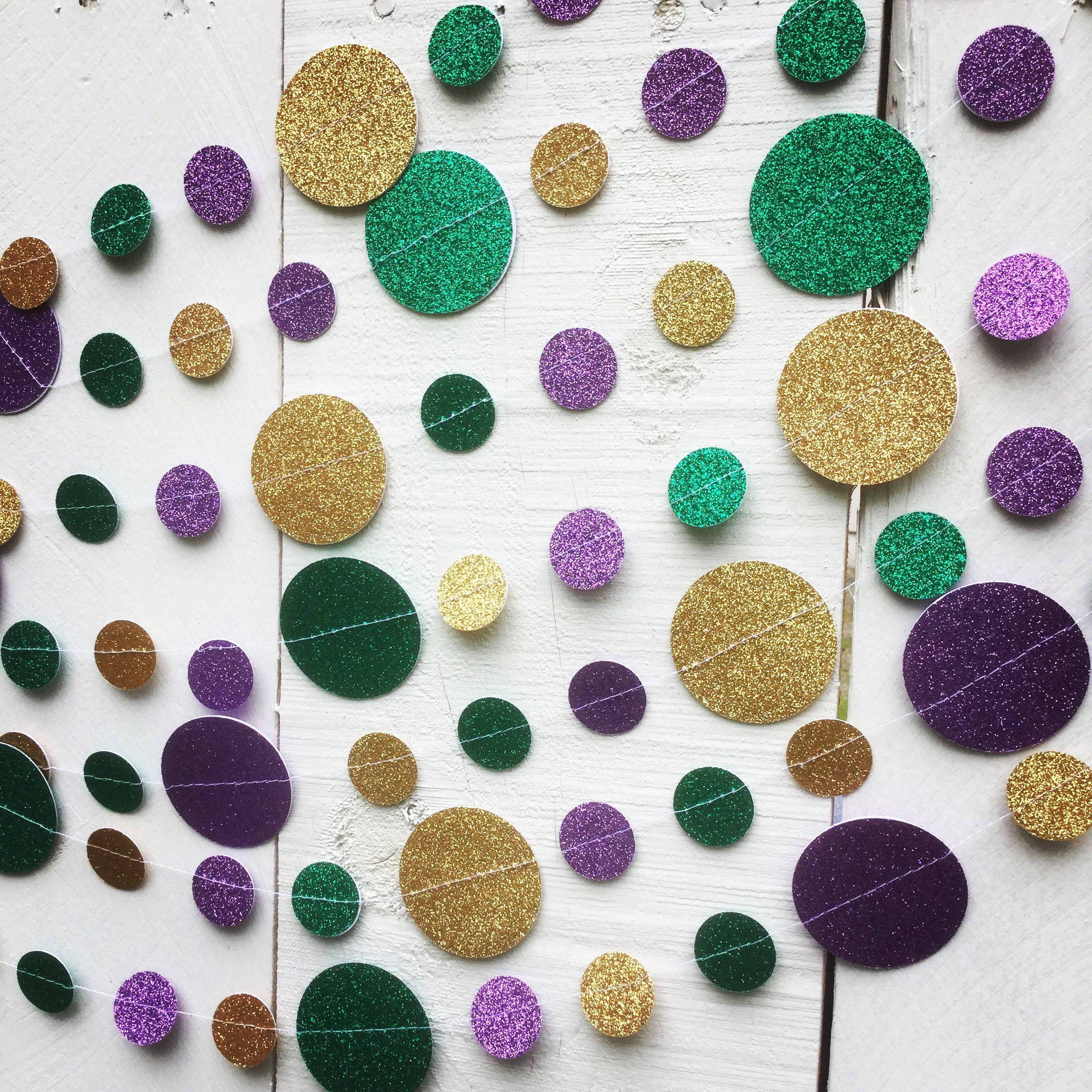 Green, gold, and purple glitter card stock circles sewn into a Mardi Gras garland decoration