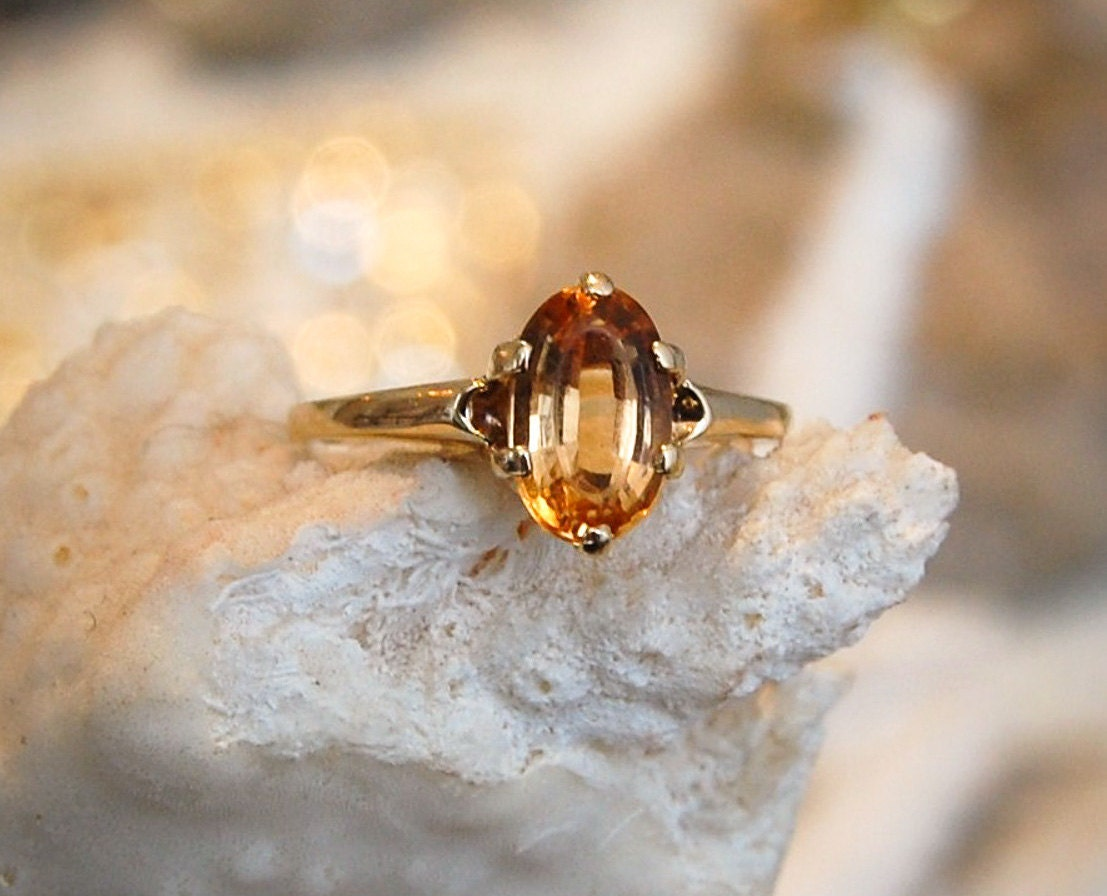 Citrine-Topaz-Gold-Solitaire-Ring-with-Amber-Golden-Hues-displayed-on-coral