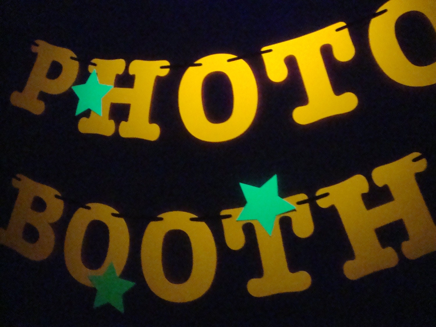 3.5 letters and stars in neon colors to spell PHOTO BOOTH