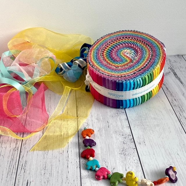 A Rolie Polie of Create Fabric by Quiet Play ready for use in the River Rapids Quilt Along - a quilt along for beginner quilters, as well as more experienced quilters. The Jelly roll is surrounded by a small elephant bracelet and soft soft chiffon ribbons.