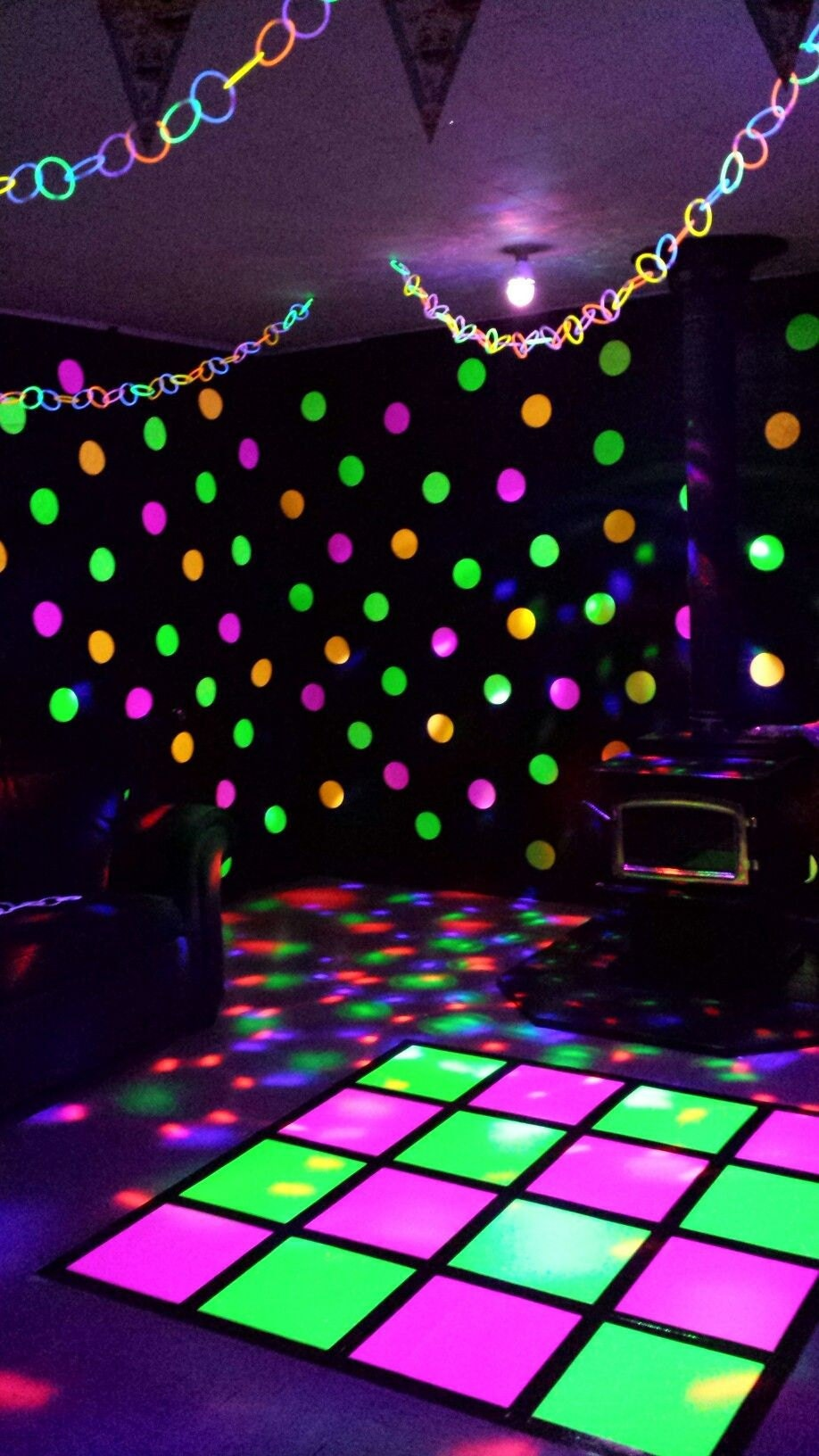 neon poster board on dance floor at a glow black light party