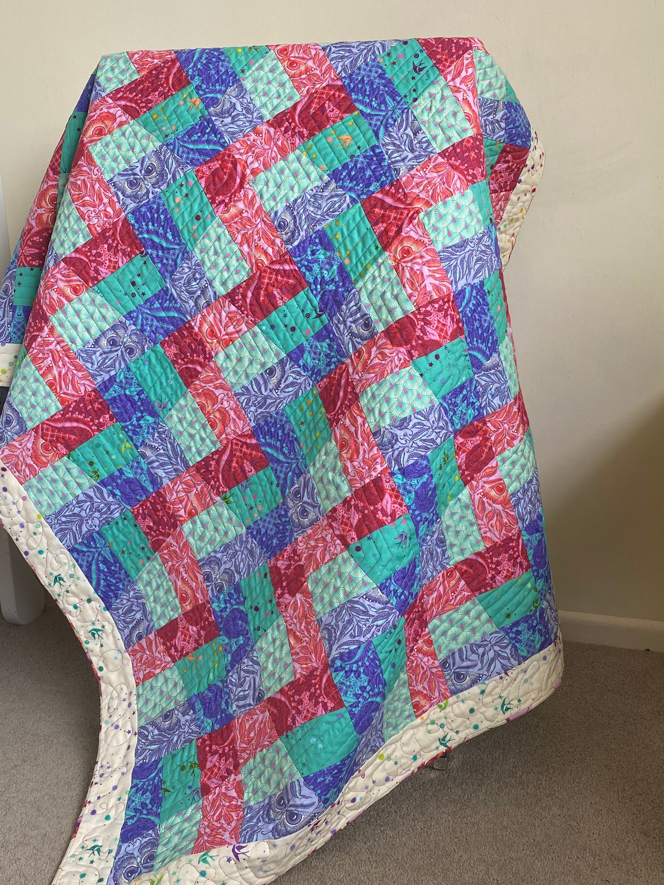 Rail Fence Quilt draped over a stand.