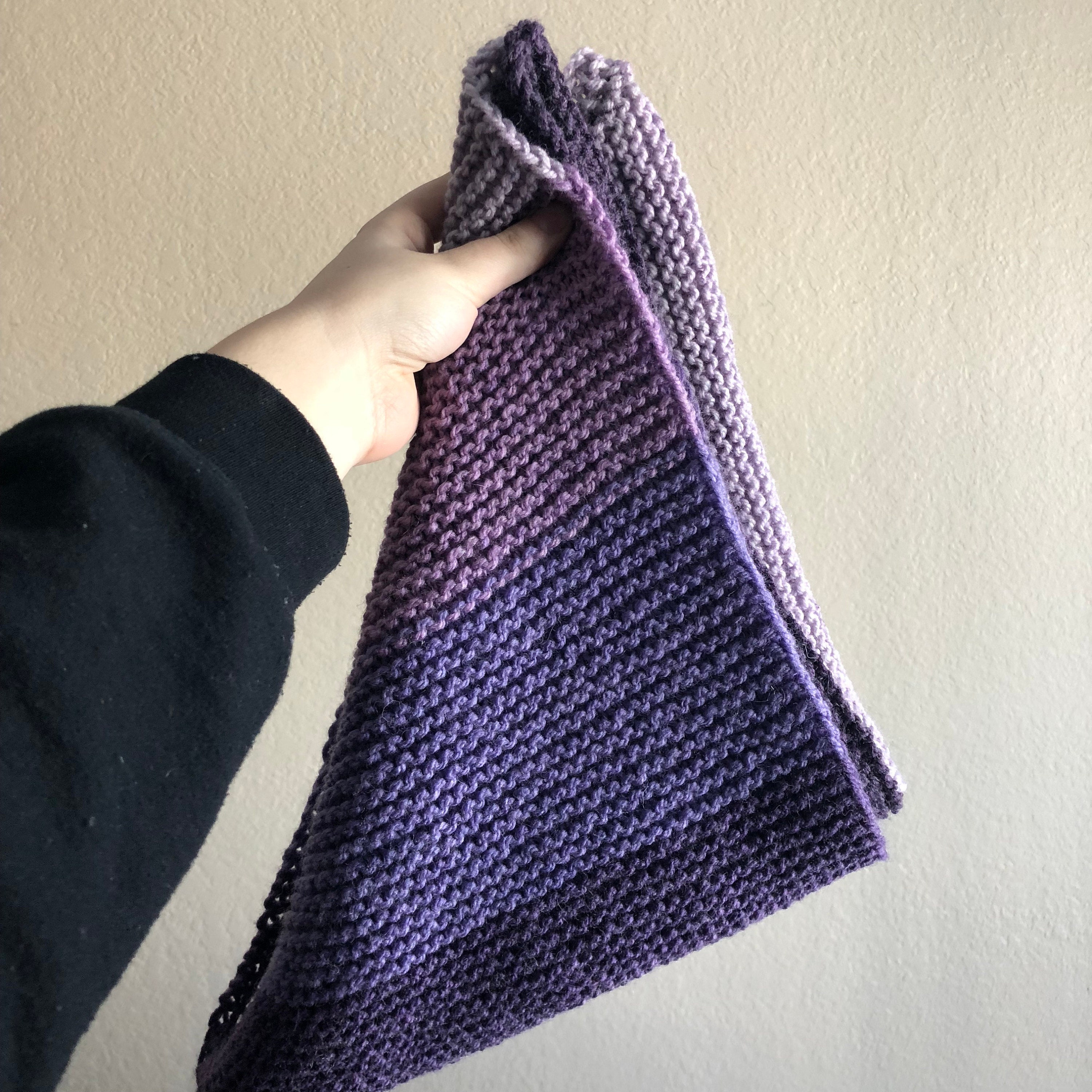 Person holding a knitted shawl
