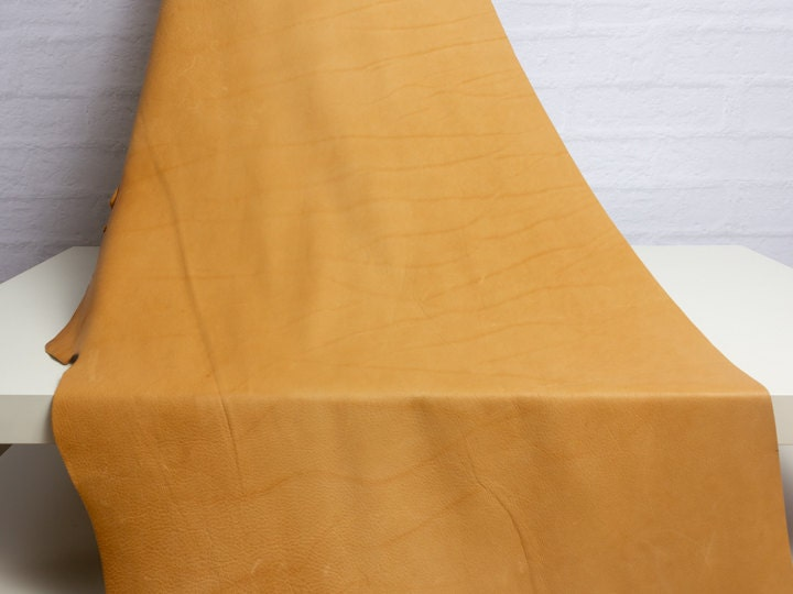 A hide of tan leather showing natural marks in the leather.