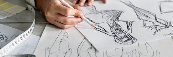 womans hands sketching fashion designs with pencil and tape measure
