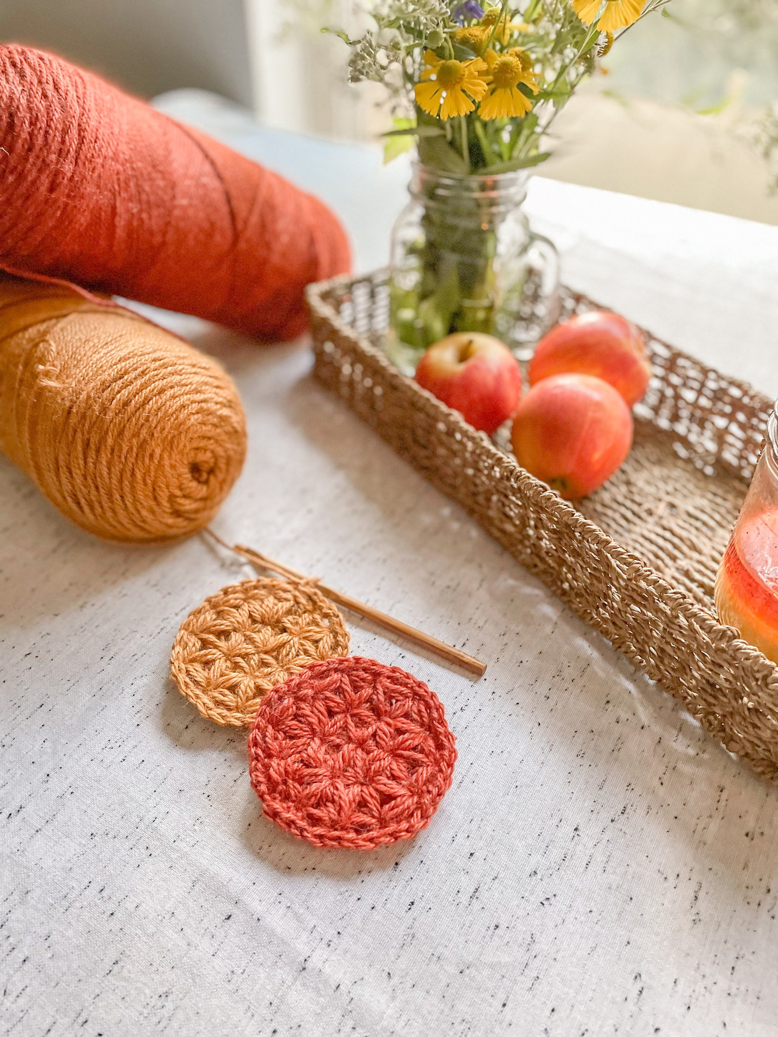 Crochet Fall Leaf Coasters, Yarn, Wildflowers, and apples in a basket