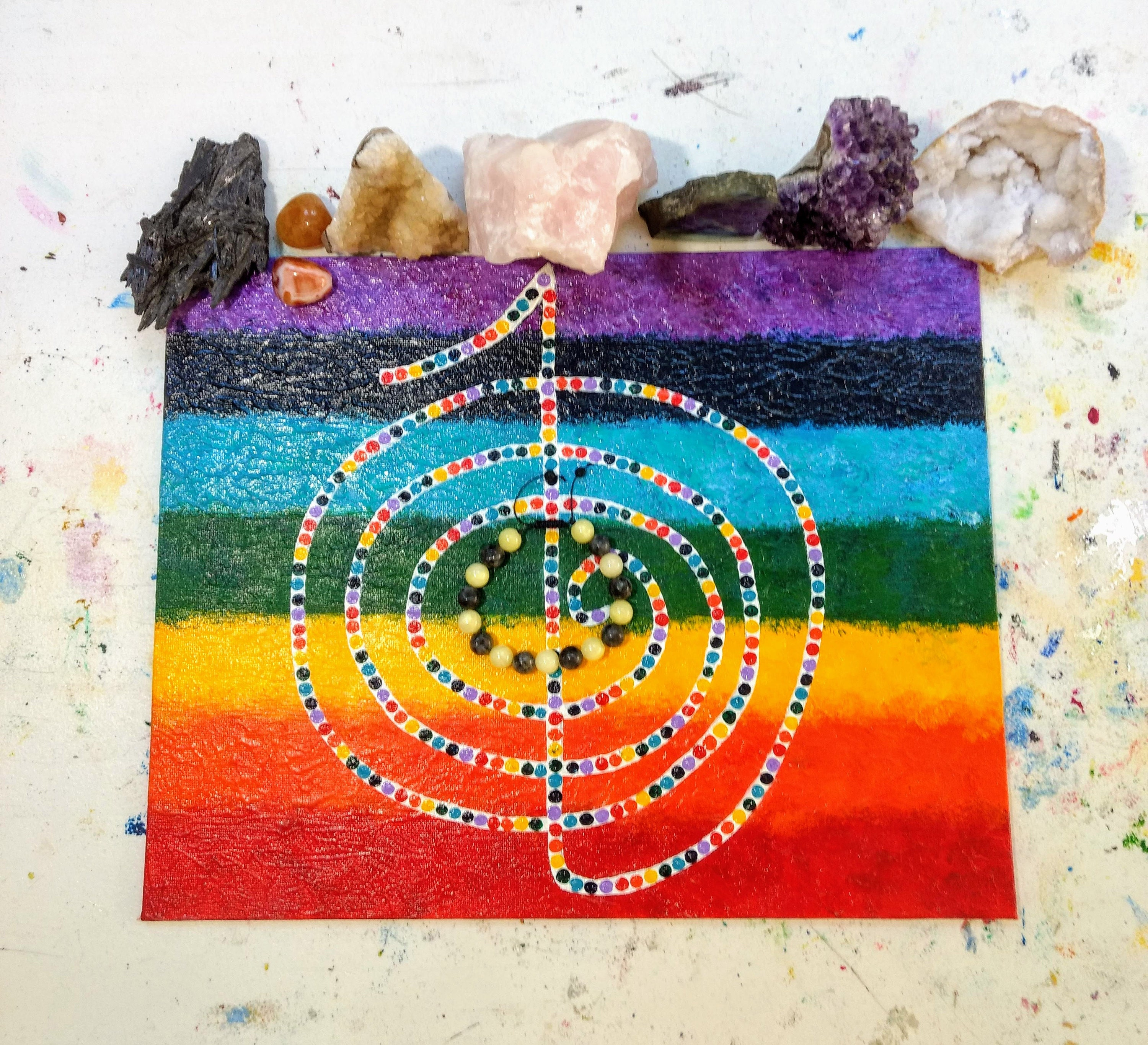 This is the Cho Ku Rei reiki symbol that I painted to put my pieces on when I reiki cleanse them. I always place the stones that I feel led to use for that particular person/sale that are good for the seven chakras at the top.