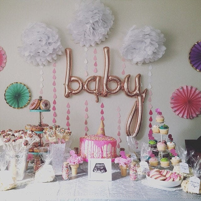 baby balloon with white poms and pink raindrop garlands behind food table for baby shower
