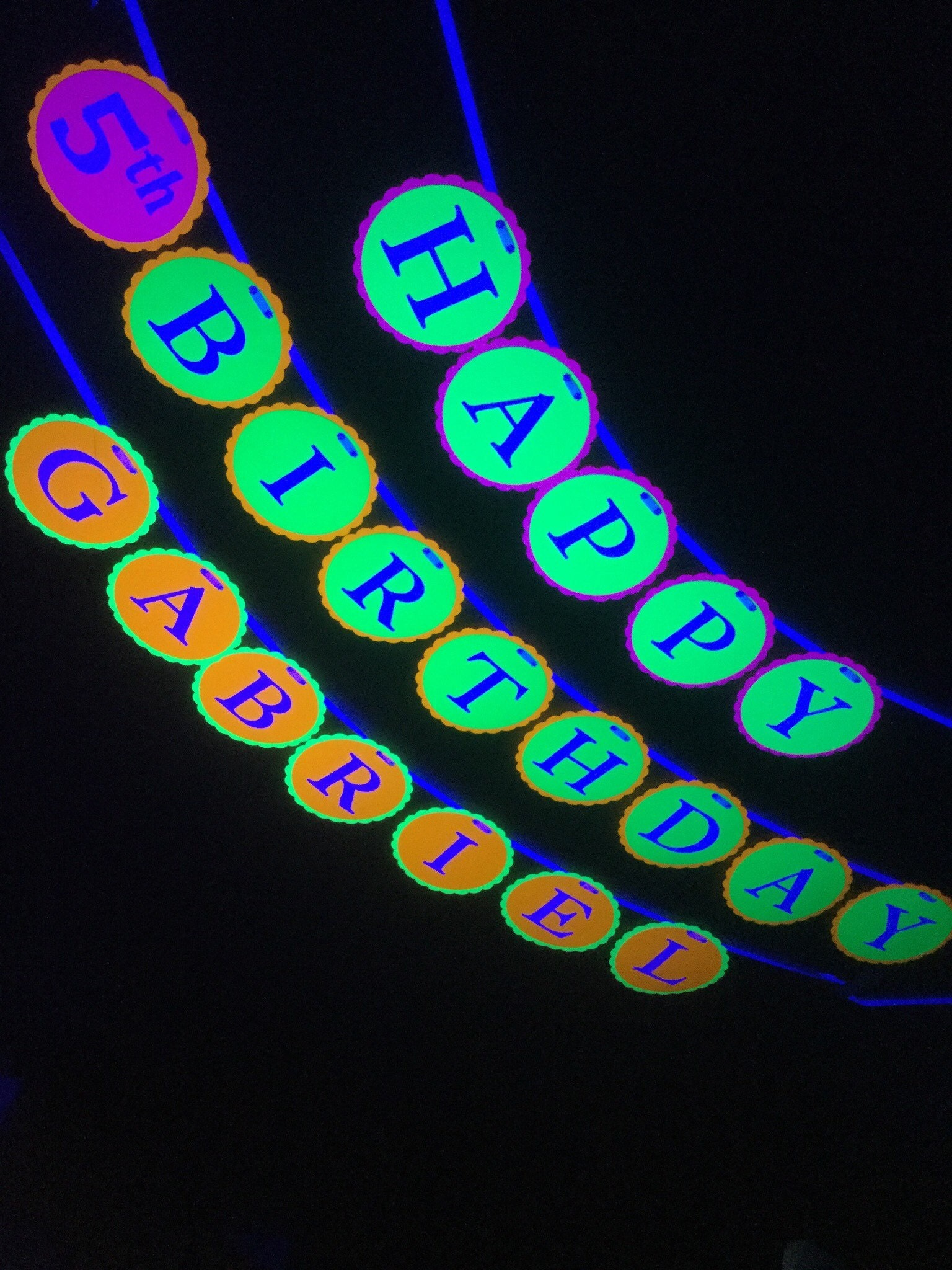 4 circles in neon colors with HAPPY BIRTHDAY GABRIEL for glow black light party
