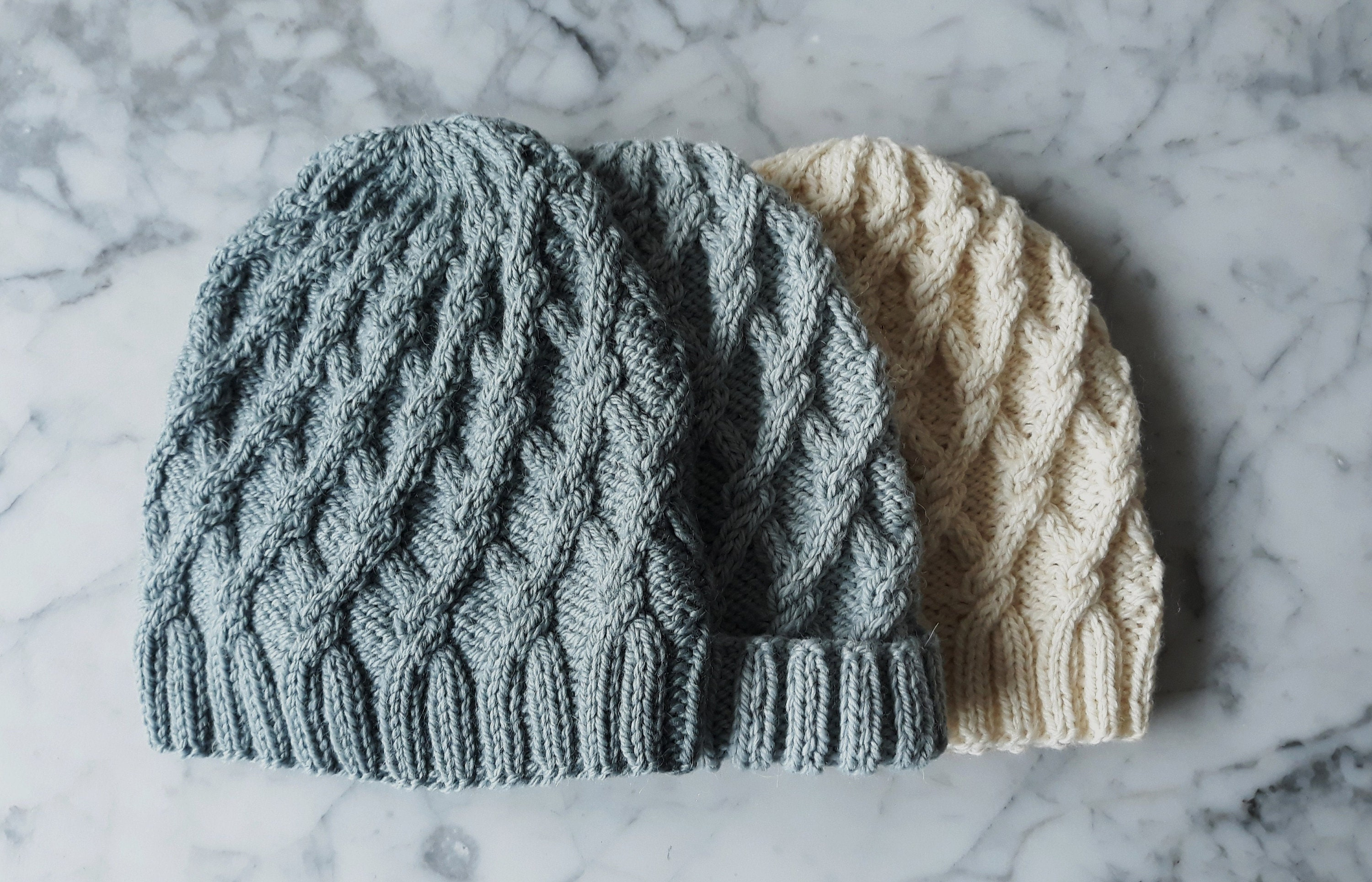 Three knitted cabled hats are laid flat, the hats are different colours: two are grey and one is creamy white.