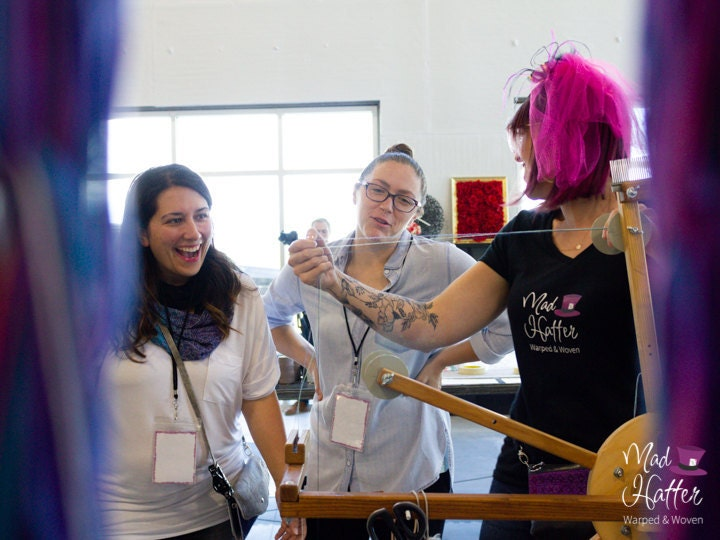 Queen Hatter is shown with two guests warping thread onto a wooden warping wheel. Queen Hatter has on a black shirt with the Mad Hatter logo on it, and a pink feathered hat. Queen Hatter and guests are looking at each other and smiling/ laughing.
