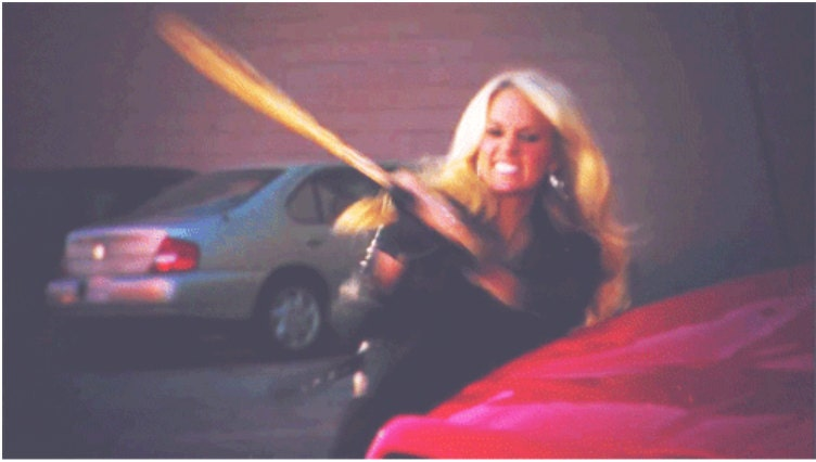 woman hitting red car with baseball bat