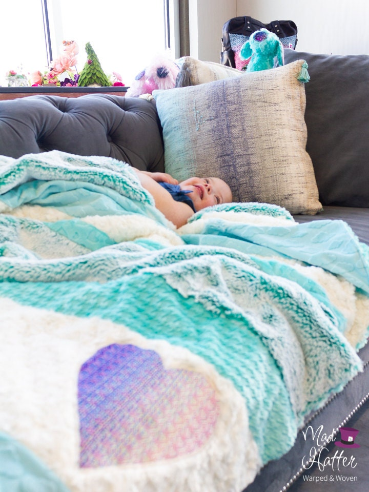 Young girl cuddled up in Mad Hatter Warped & Woven minky blanket on a grey couch.
