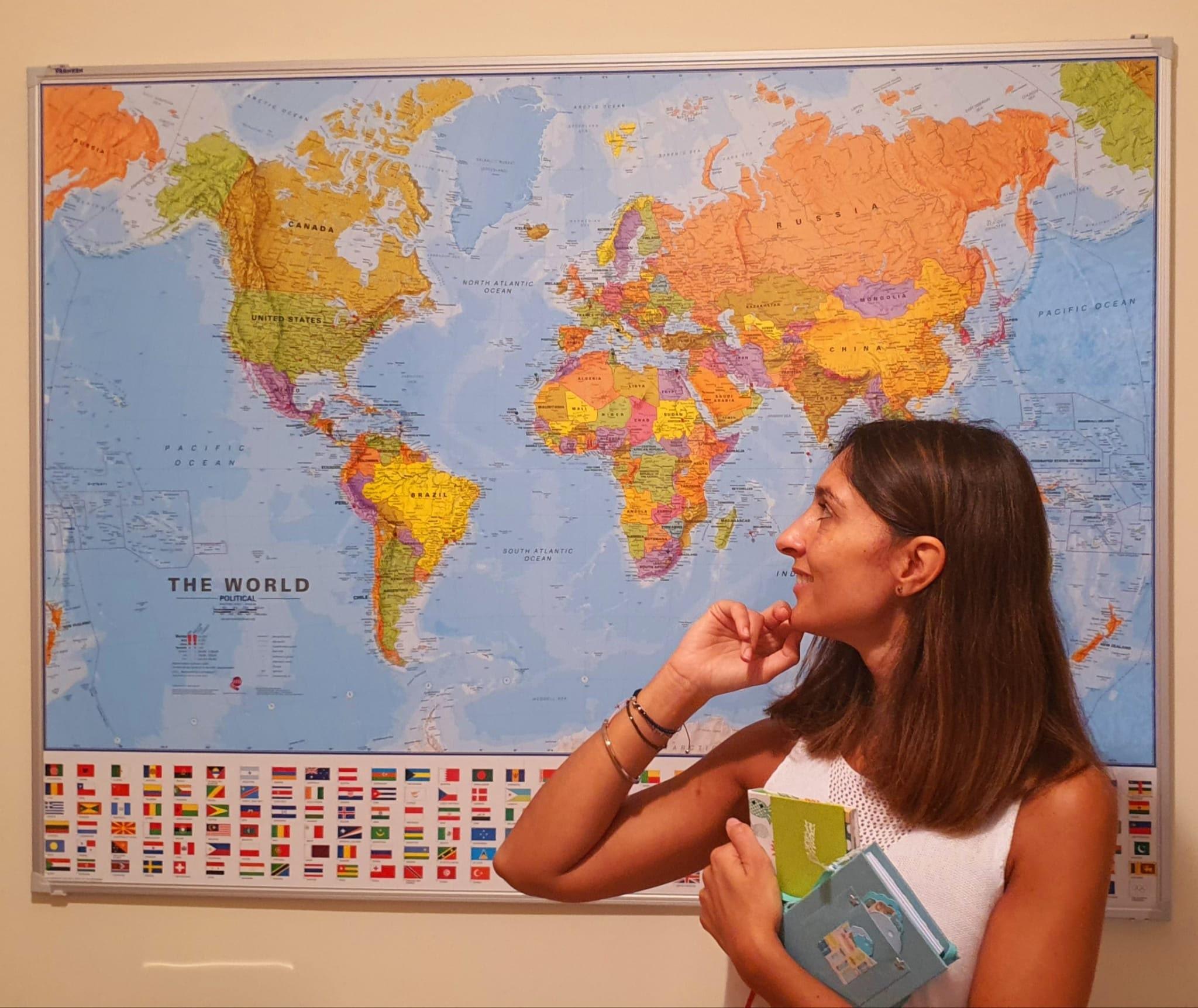 Fotografía de la periodista Tona Català con el Mapa Mundi con los paises que ha visitado