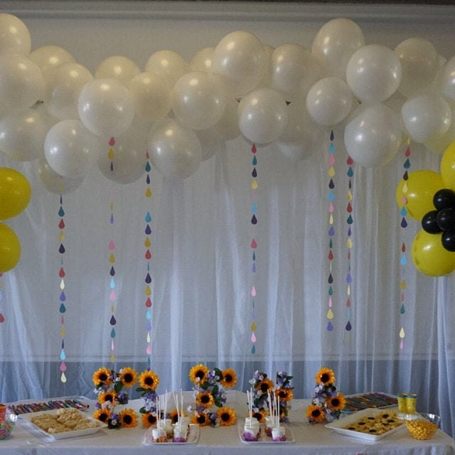 colorful raindrop garlands hanging from white balloons behind food table for bridal shower