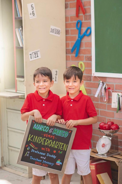 two boys holding one chalkboard